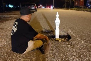 How to get authorities to fix road 101 – put a tombstone in the pothole